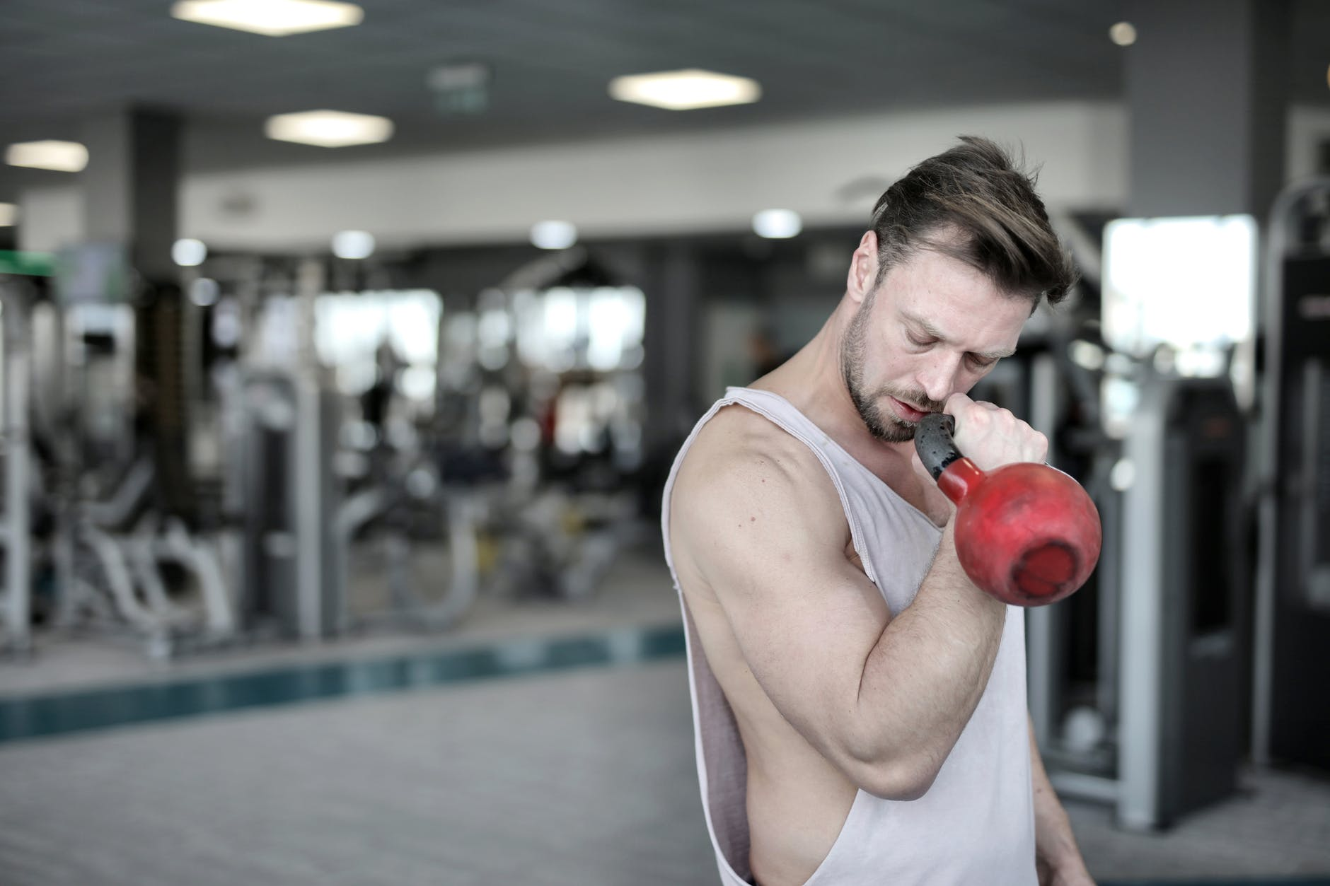 man in white tank top holding red kettlebell